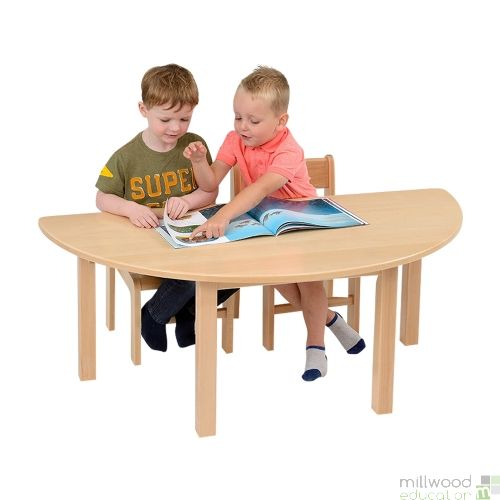 Children reading at a wooden table.
